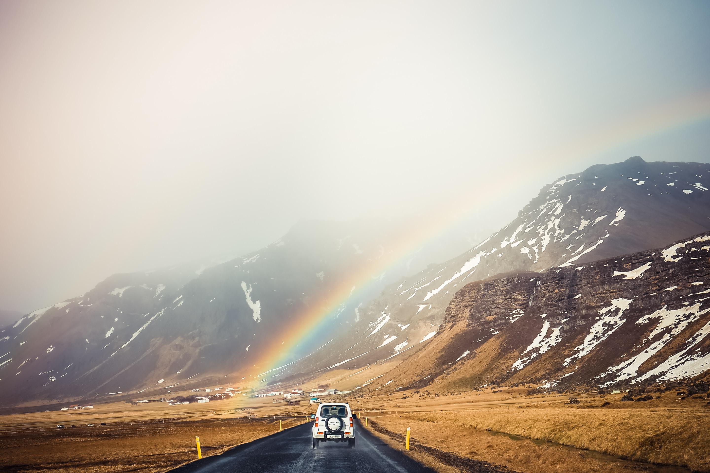 white antique car on mountain road under rainbow